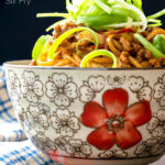 Portrait image of dan dan noodles, a Chinese stir fried minced pork recipe served in a bowl decorated with an Asian stylised flower decoration with a text overlay