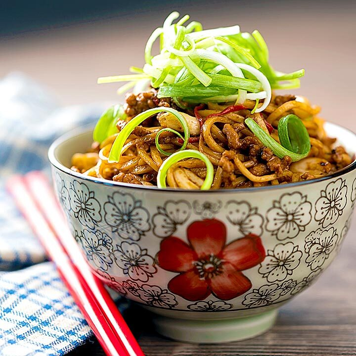 Square image of dan dan noodles, a Chinese stir fried minced pork recipe served with a spring onion garnish served in a bowl decorated with an Asian stylised flower motif