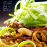 Portrait close up image of dan dan noodles, a Chinese stir fried minced pork recipe served with a spring onion garnish with a text overlay