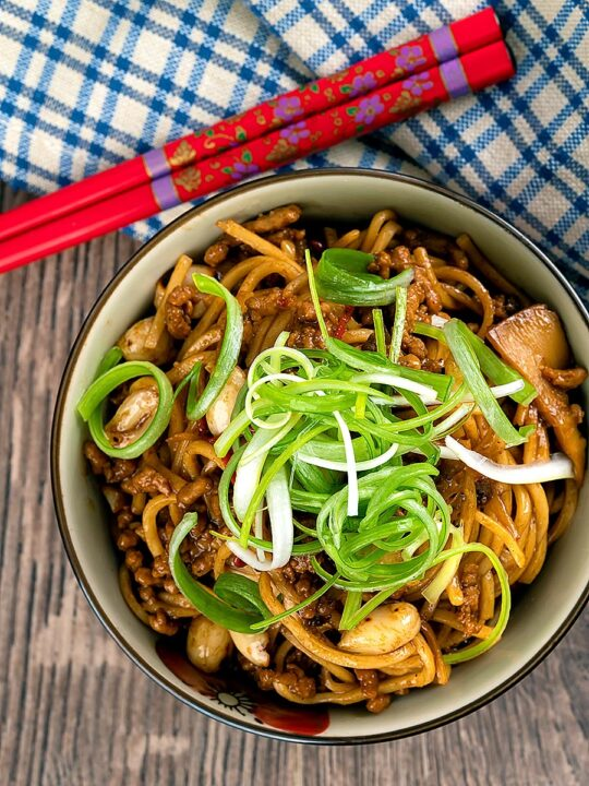 Portrait overhead image of dan dan noodles, a Chinese stir fried minced pork recipe served with a spring onion garnish