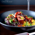 Portrait image of a beef shin osso bucco recipe served on polenta in a black bowl with a text overlay