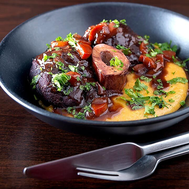 Square image of a beef shin osso bucco recipe served on polenta in a black bowl
