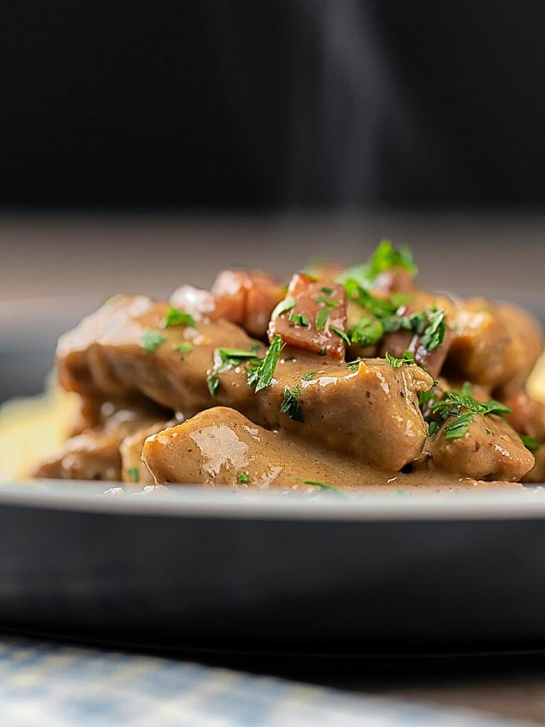 Portrait close up image of a Hungarian Pork Stew called Borsos Tokany served steaming hot with fresh parsley