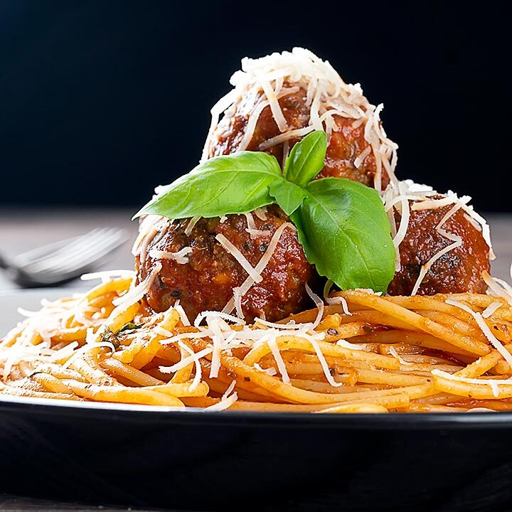 Square image of spaghetti and meatballs served with fresh basil and grated Parmesan cheese served on a white plate