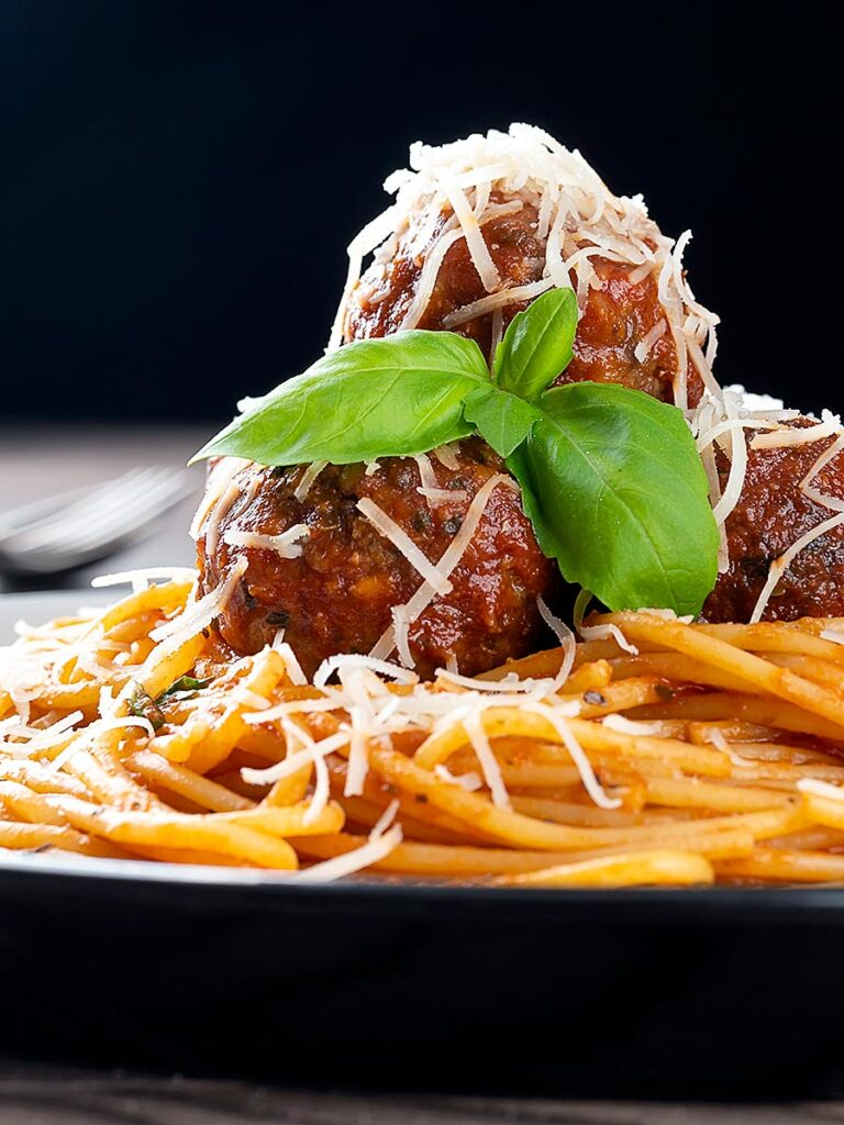 Portrait image of spaghetti and meatballs served with fresh basil and grated Parmesan cheese served on a white plate against a dark backdrop