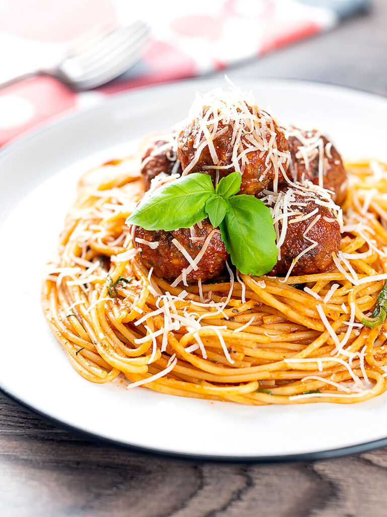 Portrait image of spaghetti and meatballs served with fresh basil and grated Parmesan cheese served on a white plate