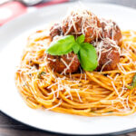 Portrait image of spaghetti and meatballs served with fresh basil and grated Parmesan cheese served on a white plate with a text overlay