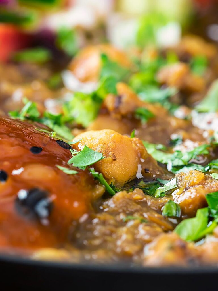 Portrait close up image of a vegan chickpea and lentil curry served with mango chutney and kachumber salad