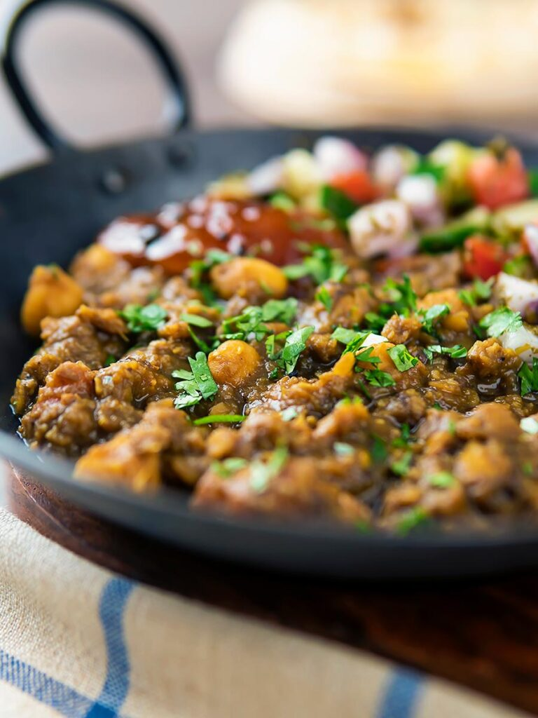 Portrait image of a vegan chickpea and lentil curry served in an iron kadai with mango chutney and kachumber salad