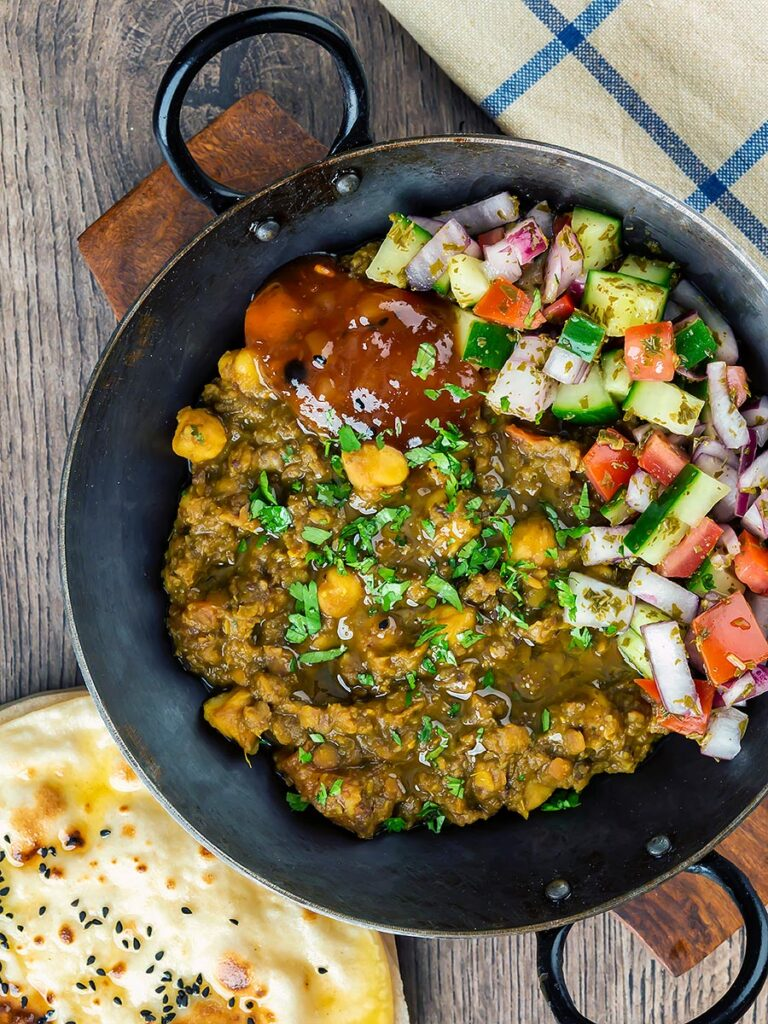 Portrait overhead image of a vegan chickpea and lentil curry served in an iron kadai with mango chutney and kachumber salad and chapatis