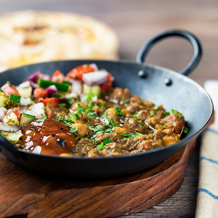 Square image of a vegan chickpea and lentil curry served in an iron kadai with mango chutney and kachumber salad