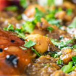 Portrait close up image of a vegan chickpea and lentil curry served with mango chutney and kachumber salad featuring a text overlay
