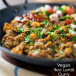 Portraitimage of a vegan chickpea and lentil curry served in an iron kadai with mango chutney and kachumber salad featuring a text overlay