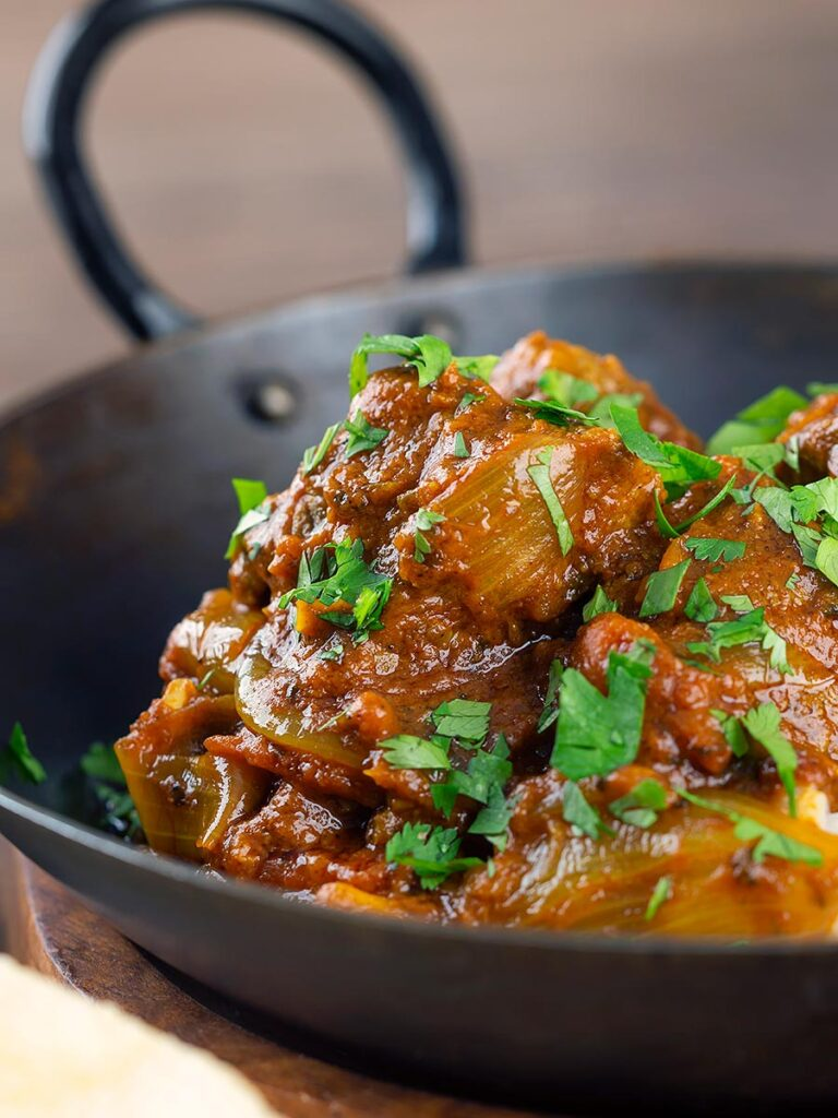 Portrait close up image of a beef bhuna curry served in an iron kadai garnished with chopped coriander