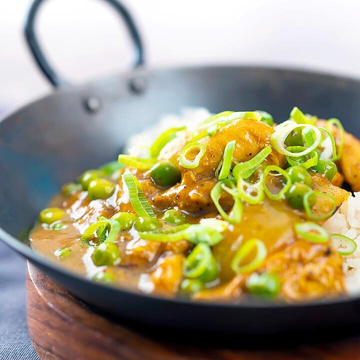 Square image of a takeaway influenced Chinese chicken curry with garden peas and spring onions