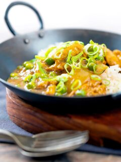 Portrait image of a takeaway influenced Chinese chicken curry with garden peas and spring onions