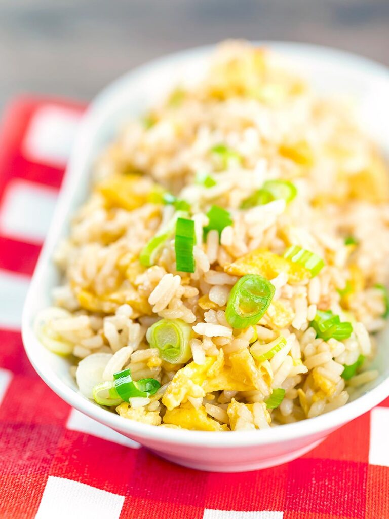 Portrait image of quick egg fried rice served in a white bowl