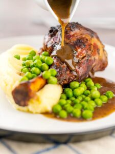 Portrait image of gravy being poured over oven braised minted lamb shanks served with mashed potatoes and peas