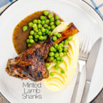Portrait overhead image of minted lamb shanks served with mashed potatoes and peas featuring a text overlay