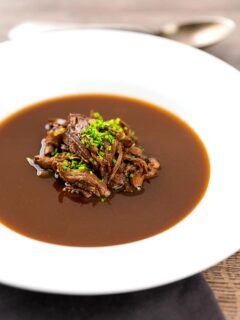 Portrait image of a British oxtail soup with a pile of shredded oxtail and snipped chives