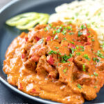 Portrait image of a Hungarian inspired pork paprikash or sertéspaprikás served with nokedli on a grey plate featuring a title overlay