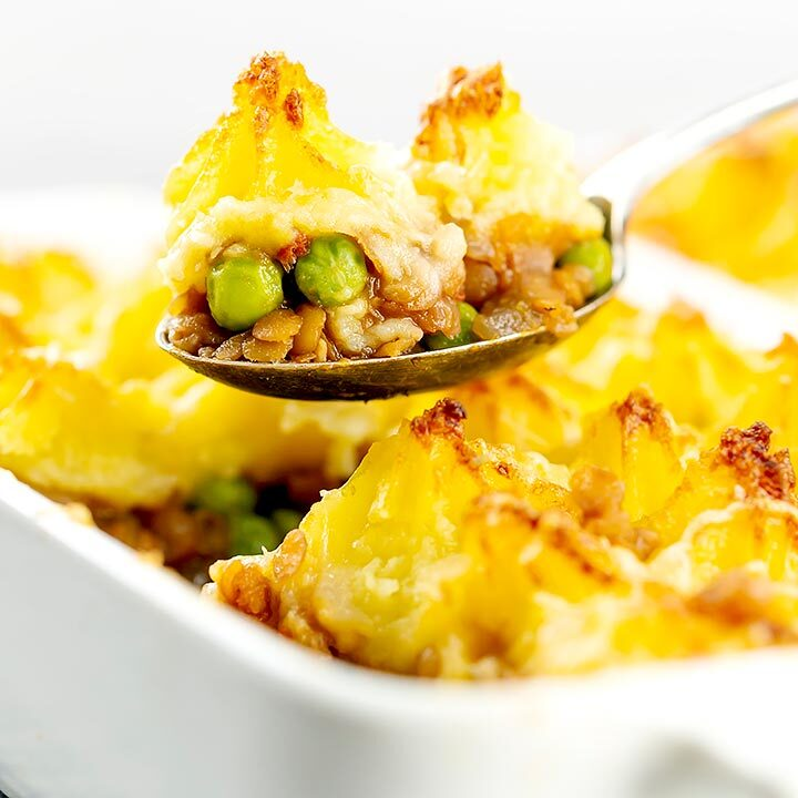 Close up square image of a spoon full of vegetarian shepherds pie or shepherdess pie being taken from a whole pie