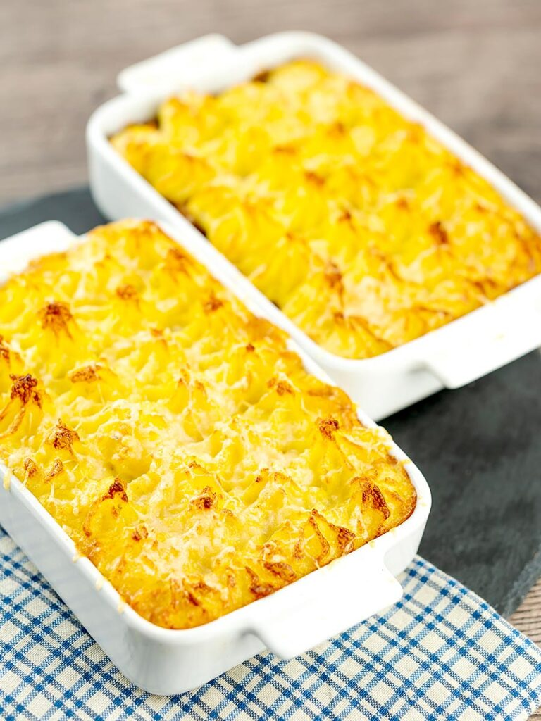 Portrait image of individual vegetarian shepherds pies or shepherdess pies served in white gratin dishes
