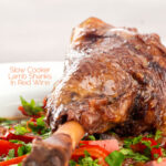 Portrait close up image of a slow cooker braised lamb shank served in a shallow white bowl with red peppers in a red wine gravy featuring a title overlay