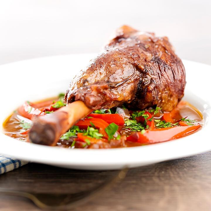 Square image of a slow cooker braised lamb shank served in a shallow white bowl with red peppers in a red wine gravy