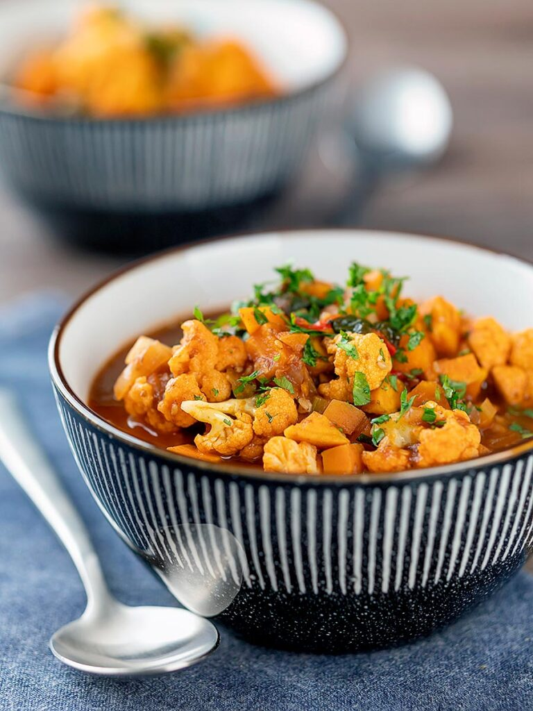 Portrait image of a spicy vegetable soup with sweet potato, cauliflower and in a harissa broth