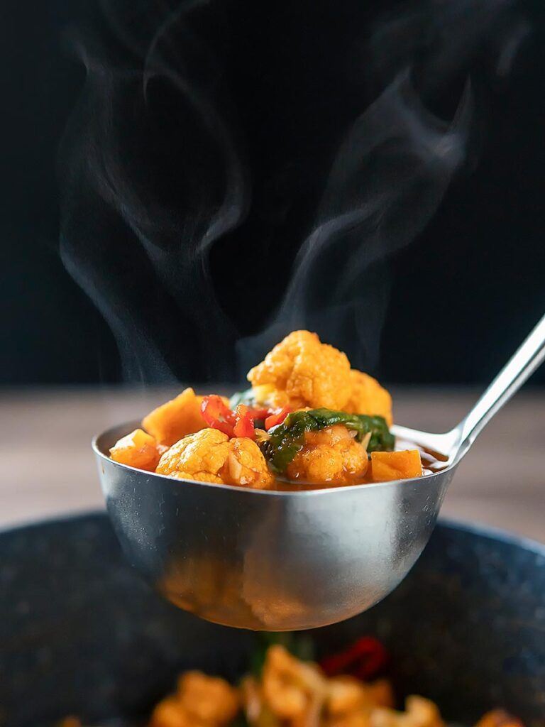 Portrait image of a steaming hot spicy vegetable soup with sweet potato, cauliflower and in a harissa broth in a ladle