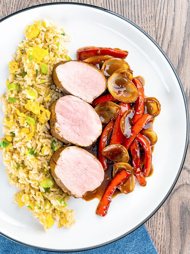 Portrait overhead of image rosy pink roasted juicy sweet and sour pork tenderloin with onions and red pepper in a rich sweet and sour sauce and egg fried rice