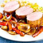 Portrait image of rosy pink roasted juicy sweet and sour pork tenderloin with onions and red pepper in a rich sweet and sour sauce and egg fried rice featuring a title overlay