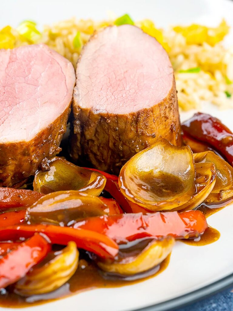 Portrait close up image of rosy pink roasted juicy sweet and sour pork tenderloin with onions and red pepper in a rich sweet and sour sauce and egg fried rice