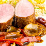 Portrait close up image of rosy pink roasted juicy sweet and sour pork tenderloin with onions and red pepper in a rich sweet and sour sauce and egg fried rice featuring a title overlay