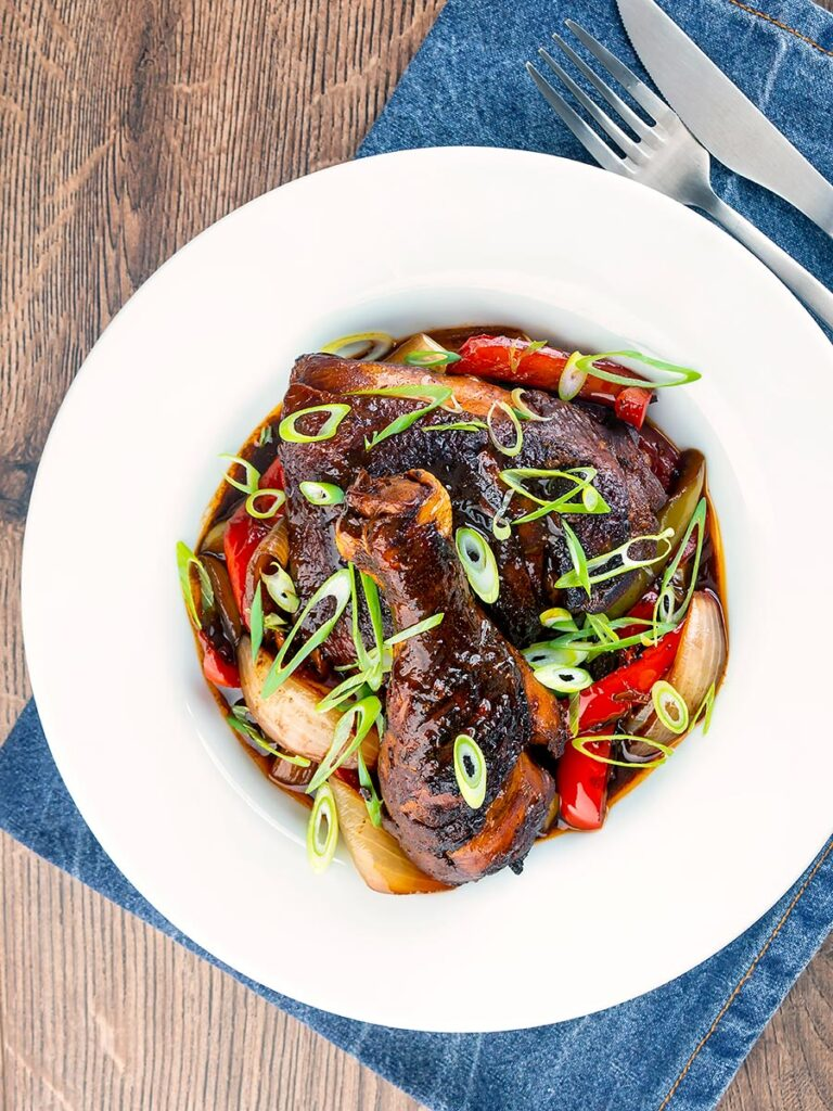 Portrait overhead image of a Jamaican brown stew chicken served in a white shallow bowl with a spring onion garnish