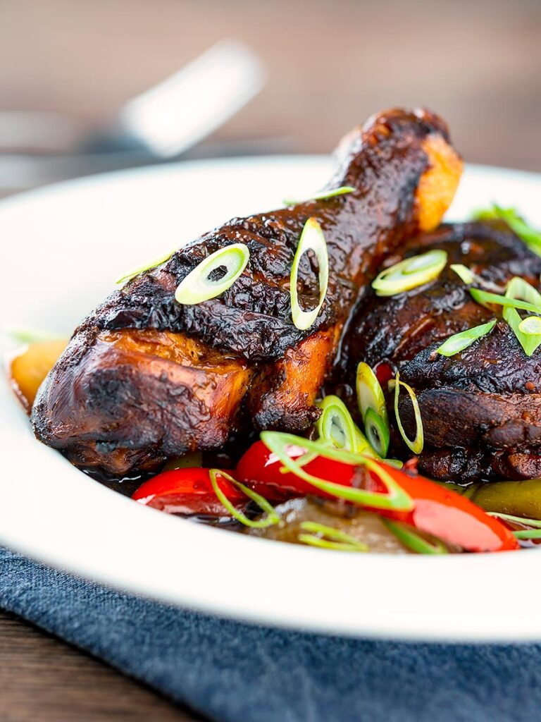Portrait image of a Jamaican brown stew chicken served in a white shallow bowl with a spring onion garnish