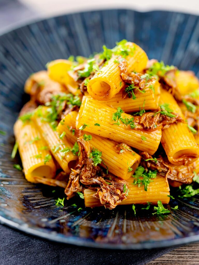 Portrait image of a shredded Venetian duck ragu served with rigatoni pasta in a mottled dark blue pasta bowl
