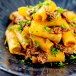 Portrait image of a shredded duck ragu served with rigatoni pasta in a mottled dark blue pasta bowl featuring a text overlay