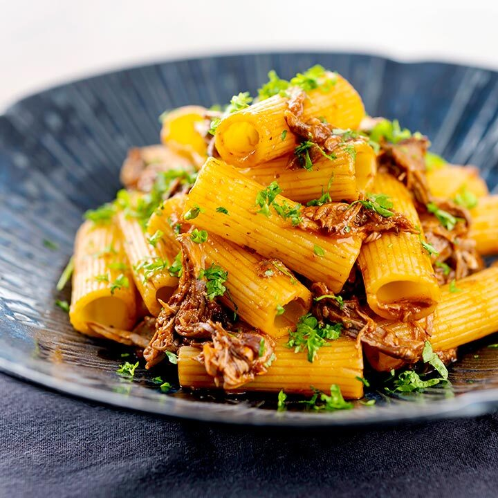 Square image of a shredded Venetian duck ragu served with rigatoni pasta in a mottled dark blue pasta bowl