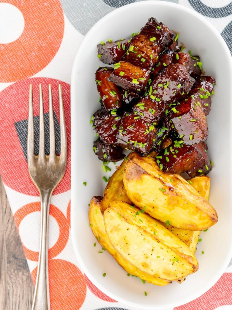 Portrait overhead image of sticky gluhwein pork belly bites served with potato wedges and snipped chives