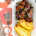 Portrait overhead image of sticky gluhwein pork belly bites served with potato wedges and snipped chives featuring a text overlay