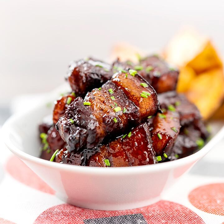 Square image of sticky gluhwein pork belly bites served with potato wedges and snipped chives