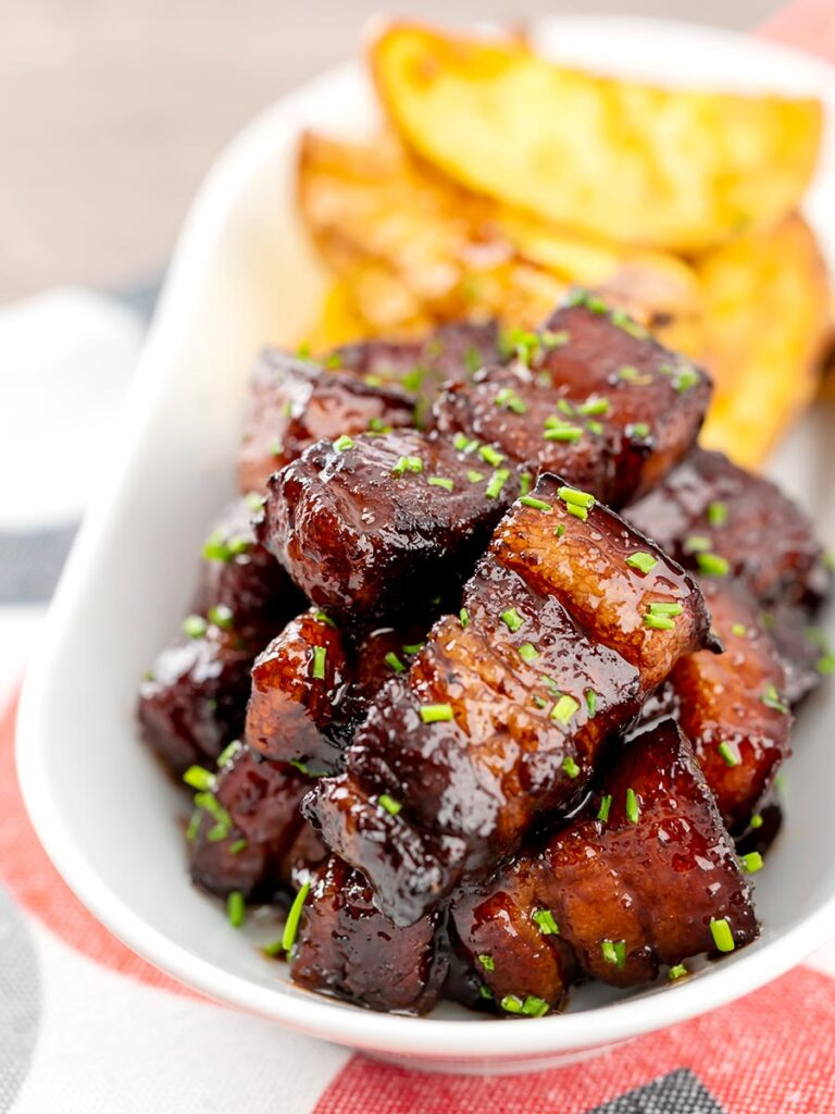 Portrait image of sticky gluhwein pork belly bites served with potato wedges and snipped chives