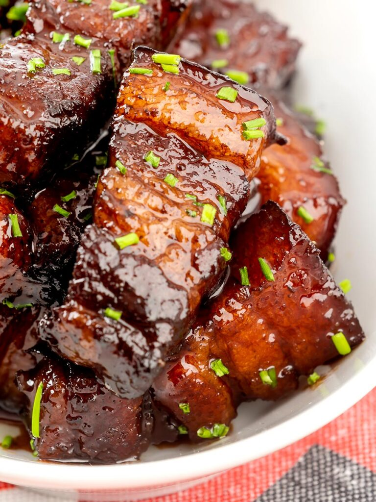 Portrait close up image of sticky gluhwein pork belly bites served with potato wedges and snipped chives