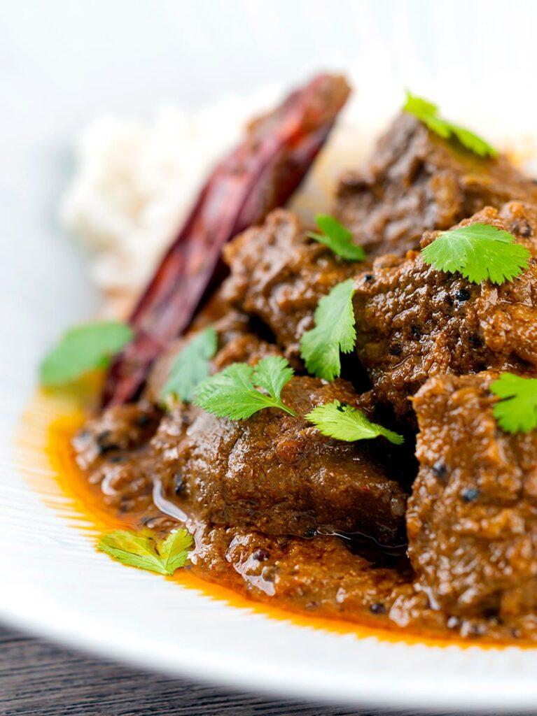 Portrait close up image of an achar gosht lamb or mutton curry served on a white plate with whole chilies and coriander leaves