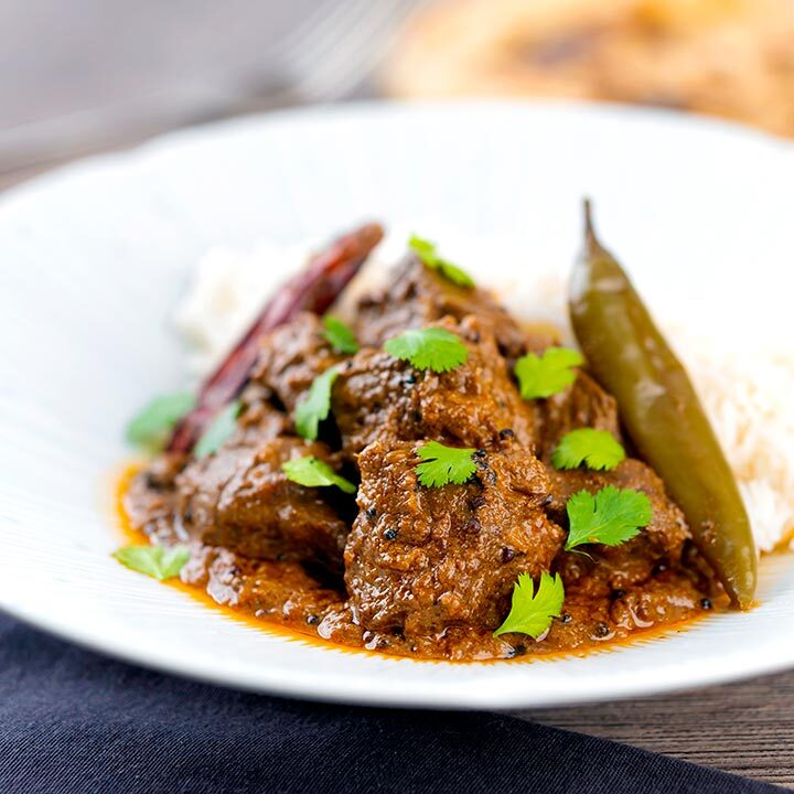 Square image of an achar gosht lamb or mutton curry served on a white plate with whole chilies, basmati rice and coriander leaves