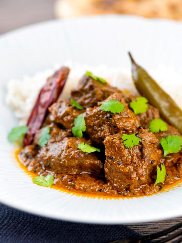 Portrait image of an achar gosht curry served on a white plate with whole chilies, basmati rice