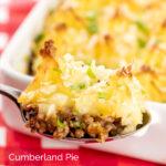 Portrait close up image of a spoonful of cheesy cumberland pie with a whole pie served in a white gratin dish in the background with a title overlay