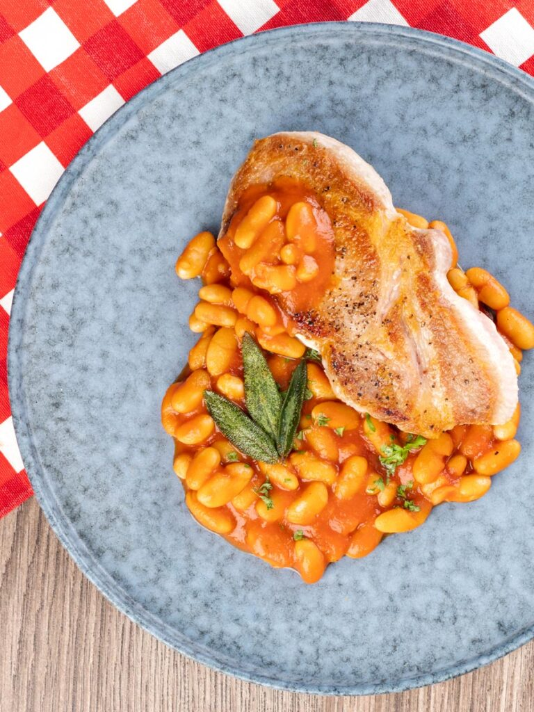 Portrait overhead image of Fagioli all'uccelletto or Italian Baked Beans served with a pork loin steak and crispy fried sage leaves